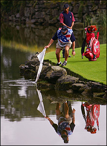 Woods' caddie Steve Williams drops his nine iron in the water