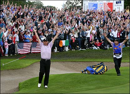 Darren Clarke throws his club in the air and caddie Billy Foster runs to embrace him after his winning putt