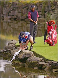 Steve Williams attempts to retrieve the nine-iron as Tiger Woods looks on