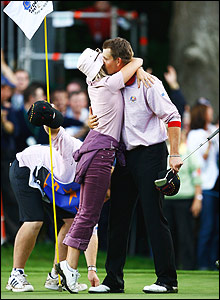 Henrik Stenson is hugged by girlfriend Emma Lofgren after holing his putt on the 15th green