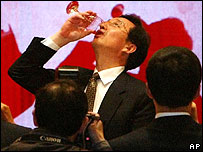 File photo of Chen Liangyu drinking from a cup of local rice wine at a banquet in Shanghai in May 2005