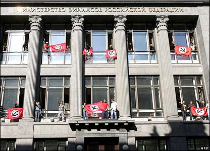 Members of the Russian National-Bolshevik Party hold flags as they stand at the windows of the finance ministry during a protest in Moscow