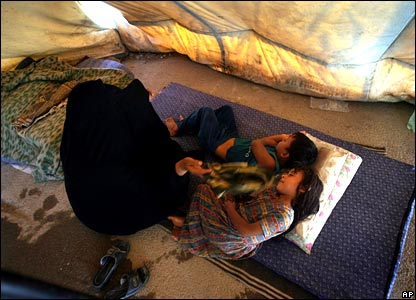 Iraqi mother fans children as they sleep in their tent in Baghdad