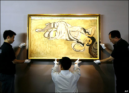 Workers hang a painting by French impressionist Henri Matisse entitled Lorette with Coffee Cup painted in 1917 during an exhibition presented by Centre Pompidou, Paris, in Hong Kong's Museum of Art