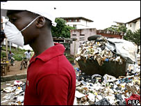 Man walks by rubbish dump in Abidjan, Ivory Coast