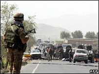 A soldiers of the NATO-led International Security Assistance Force (ISAF) (L) stand guard while others inspect the site of a bomb blast on the outskirts of Kabul