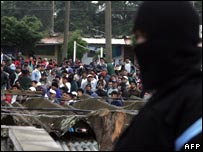 A masked security forces member guards prisoners at Pavon jail in Guatemala