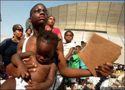 Teenager holding a baby outside the Superdome in the aftermath of Hurricane Katrina