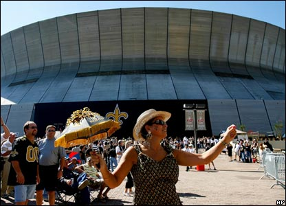 Sports fan dancing in front of the New Orleans Superdome before the match