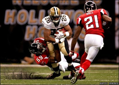 Atlanta Falcons player tackling New Orleans Saints runningback