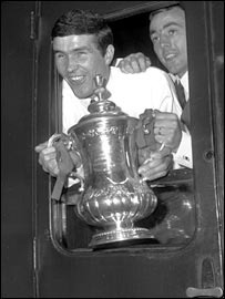 Ron Yeats and Ian St John show off the FA Cup on the train from Euston to Liverpool