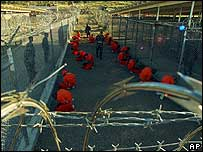 Detainees in orange jumpsuits at Camp X-Ray at Naval Base Guantanamo Bay