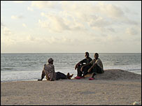 Young men relax on a beach in The Gambia