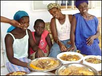 Women in The Gambia invite guests to eat food they've just prepared