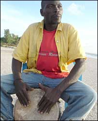 A bumster plays the drums on a beach in The Gambia