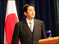 Japan's new Prime Minister Shinzo Abe steps on the podium to open his first press conference after forming his Cabinet in Tokyo on Tuesday night, Sept. 26, 2006.