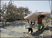 People rescue household items from the mud in Sidoarjo, East Java, Indonesia