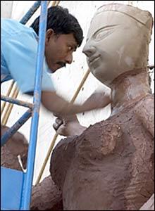 A craftsman coats the Durga idol with clay