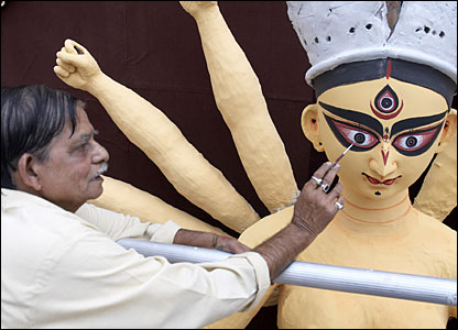 A craftsman paints eyes on the Durga idol
