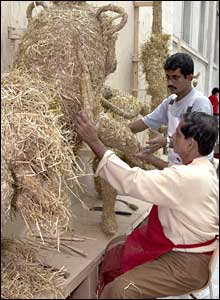 Craftsmen work on the straw model of the lion