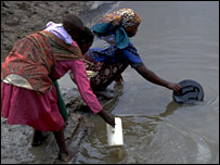 Two women fetch water from a river in Mozambique