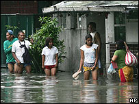 Residents wade through a flooded street in Manila