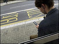 Man watching mobile TV at bus stop