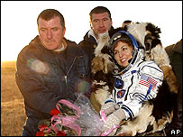 Russian ground staff carry Ms Ansari after touchdown
