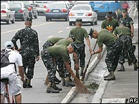 Philippine Marines sweep debris from a street in Manila