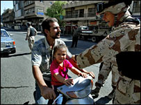 An Iraqi soldier talks to a man and a child at a Baghdad checkpoint