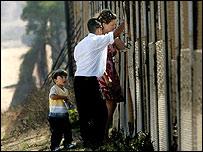Familiares se saludan a trav�s de muro en frontera entre EE.UU. y M�xico