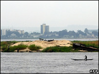 A Congolese fisherman passes in front of the Brazzaville skyline in the harbour of Kinshasa