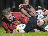 Anthony Horgan of Munster scores despite the tackle of Neil Best