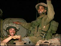 Israeli soldiers smile after crossing from Lebanon into Israel