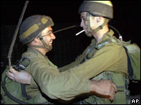 Israeli soldiers hug after crossing from Lebanon into Israel