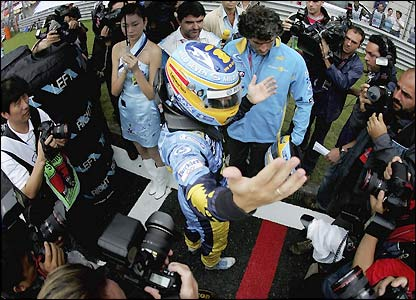 Fernando Alonso is surrounded by photographers