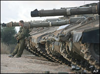 An Israeli soldier leans on a tank after Israeli troops crossed back into northern Israel from Lebanon, near the town of Avivim