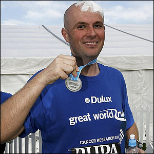 Cancer survivor Findlay Young displays his medal after completing the race