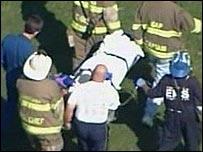 Trabajadores de emergencia retiran a las v�ctimas en camillas.