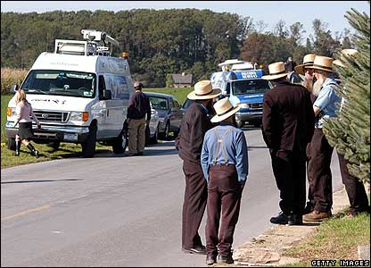 Amish people gather behind a police cordon