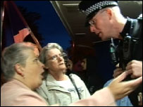 An angry resident confronts a police officer during the attempted raid