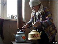 Georgian woman heating kettles at a wood stove