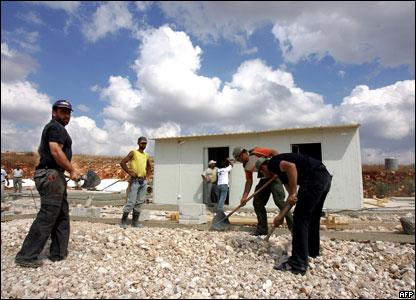 Рабочие устанавливают сборные домики, подаренные Ливану Саудовской Аравией, чтобы расселить тех, чьи дома были разрушены израильскими ВВС