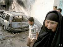 A woman walks past a burnt vehicle after a gunbattle in Baghdad. File photo