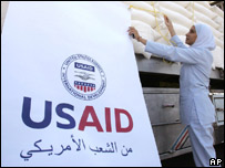 A woman examines sacks of emergency aid for Lebanon