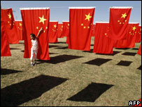 A girl plays among flags in a park in Beijing, China