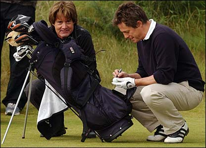 Kyle MacLachlan watches on as Hugh Grant signs a ball