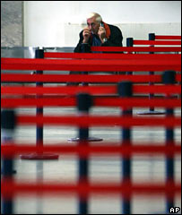A man waits in Tbilisi airport after transport links are suspended on 3 October 2006