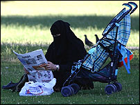 A woman reads a newspaper in Regents Park