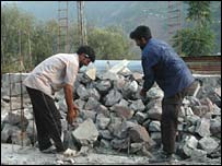 Imtiaz Kashmiri and a neighbour move stones
